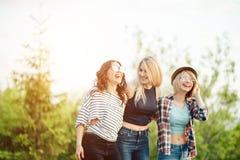 Drie jonge vrouwelijke vrienden die op park lopen jonge vrouwen die op de zomerdag wandelen Stock Afbeeldingen