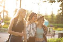 Drie jonge vrouwelijke vrienden die op park lopen jonge vrouwen die op de zomerdag wandelen Stock Foto's