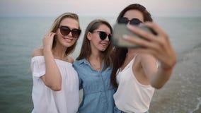 Drie jonge vrouwen die een selfie op het strand met een overzeese mening nemen De vrienden glimlachen het bekijken de camera Meis stock footage