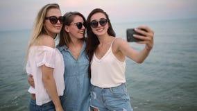 Drie jonge vrouwen die een selfie op het strand met een overzeese mening nemen De vrienden glimlachen het bekijken de camera Meis stock videobeelden