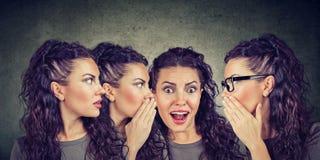 Drie jonge vrouwen die elkaar fluisteren en aan een geschokt verbaasd meisje stock foto's