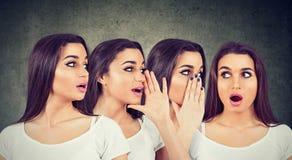 Drie jonge vrouwen die elkaar fluisteren en aan een geschokt verbaasd meisje in het oor royalty-vrije stock foto's