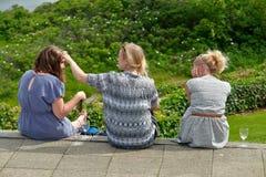 Drie jonge vrouwen die hebbend goede tijd zitten Stock Foto's