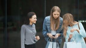 Drie jonge vrouwen die hun nieuwe aankopen met elkaar delen stock videobeelden