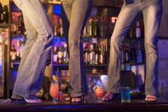 Drie jonge vrouwen die op een staafteller dansen Stock Foto's