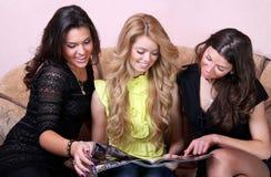 Drie jonge vrouwen die tijdschrift kijken Stock Foto's