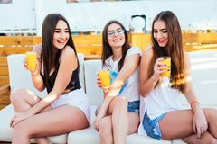 Drie jonge vrouwen drinken cocktails bij de zitting van de poolpartij op zitkamer ontspannen bij de toevlucht van de de zomerroep royalty-vrije stock afbeeldingen