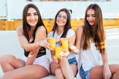 Drie jonge vrouwen drinken cocktails bij de zitting van de poolpartij op zitkamer ontspannen bij de toevlucht van de de zomerroep stock afbeelding