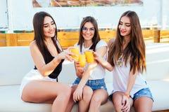 Drie jonge vrouwen drinken cocktails bij de zitting van de poolpartij op zitkamer ontspannen bij de toevlucht van de de zomerroep royalty-vrije stock foto's
