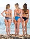 Drie jonge vrouwen van terug in bikini stock fotografie