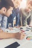 Drie jonge zakenlieden die bij lijst leunen en bij project zaken samenwerken stock afbeelding