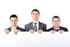 Drie jonge zakenlieden steunen een groot leeg teken Royalty-vrije Stock Afbeelding