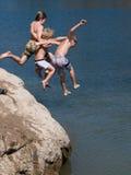 Drie Jongens die in Meer springen Stock Afbeelding
