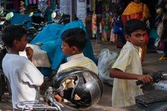 Drie jongens die met geparkeerde motoren in overvol stad-Ce spelen stock afbeelding