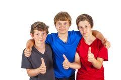 Drie jongens en vrienden tonen duimen Stock Afbeeldingen