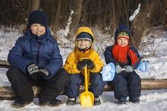 Drie jongensspel op sneeuw Stock Foto's