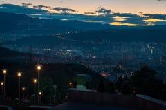 Drie jongeren die bovenop de heuvel zitten die de hoofdstad van Georgië, Tbilisi overzien terwijl de zon achter de heuvel daalt stock fotografie
