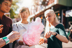 Drie jongeren die katoen delen candyfloss royalty-vrije stock afbeeldingen