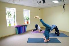 Drie jongeren die yoga doen bij geschiktheidsstudio stock afbeeldingen