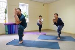 Drie jongeren die yoga doen bij geschiktheidsstudio royalty-vrije stock fotografie