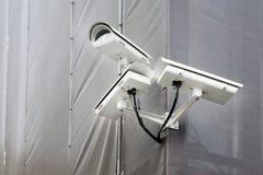 Drie kabeltelevisie-camera's op hoek van de bouw onder restauratie of vernieuwing in openlucht Veiligheidscamera's op muur van de stock foto's