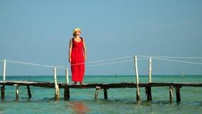 Drie kaders in video Mooie vrouw die onderaan pijler in lange rode kleding lopen De vrouw de reiziger loopt op een pijler met stock video