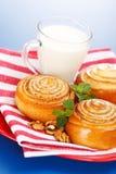 Drie kaneelbroodjes en kruik melk op rode plaat Royalty-vrije Stock Afbeeldingen
