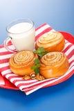 Drie kaneelbroodjes en kruik melk op rode plaat Stock Foto's