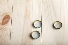 Drie kappen van bier op een houten raad, stock foto's
