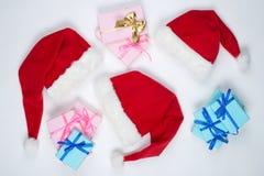 Drie kappen van Santa Claus en heden liggen op een witte lijst stock foto