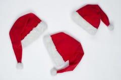 Drie kappen van Santa Claus liggen op een witte lijst royalty-vrije stock afbeeldingen