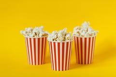 Drie kartonemmer met bioskoopsnack popcorn en rode koppen op kleuren gele achtergrond Ruimte voor tekst stock afbeelding