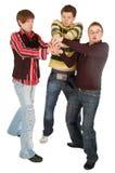 Drie kerels die iets in hun handen houden Stock Foto's