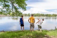 Drie kerels die zich door het water in park het besteden kwaliteitsti bevinden stock fotografie