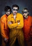 Drie kerels in oranje uniformen stock afbeeldingen