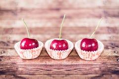 Drie kersen op cupcakevoeringen Stock Afbeeldingen
