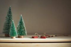 Drie Kerstbomen op een houten opmaker Het comfortabele stilleven van de huiswinter Gestemd, exemplaarruimte stock afbeeldingen