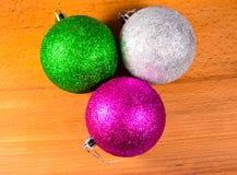 Drie Kerstmisballen op houten lijst Stock Afbeeldingen