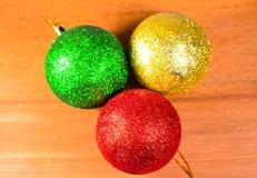 Drie Kerstmisballen op houten lijst Stock Foto's