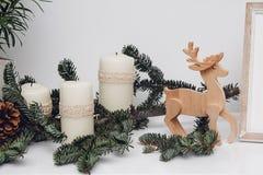 Drie Kerstmiskaarsen, pinecone, snuisterijen, tak van pijnboom, gsarland en houten herten op de witte lijst Viering en royalty-vrije stock afbeeldingen