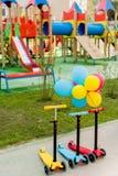 drie kinderachtige die schopautopedden in rij met kleurrijke luchtballons worden geplaatst stock fotografie