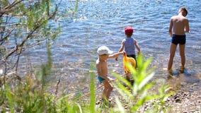 Drie kinderen bevinden zich op de Bank van een bergrivier Zij werpen rotsen bij de rivier De broers besteden de zomervakantie stock footage