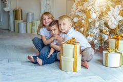 Drie kinderen dichtbij Kerstboom thuis stock afbeeldingen
