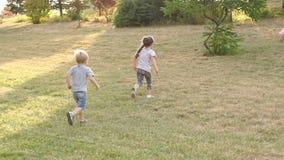Drie kinderen die in het Park op een droog gras lopen stock video
