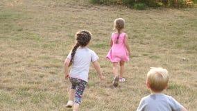 Drie kinderen die in het Park op het gras lopen stock footage