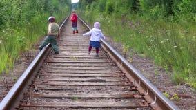 Drie kinderen die op spoorweg in bos lopen stock footage