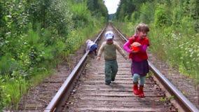 Drie kinderen die op spoorweg spelen stock video