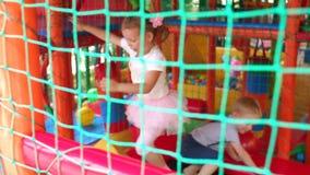 Drie kinderen die op trampoline op speelplaats springen stock video