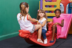 Drie kinderen die op tuimelschakelaar schommelen Royalty-vrije Stock Afbeelding