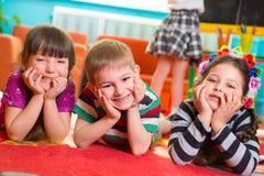 Drie kinderen die op vloer met handen onder wangen liggen Stock Foto